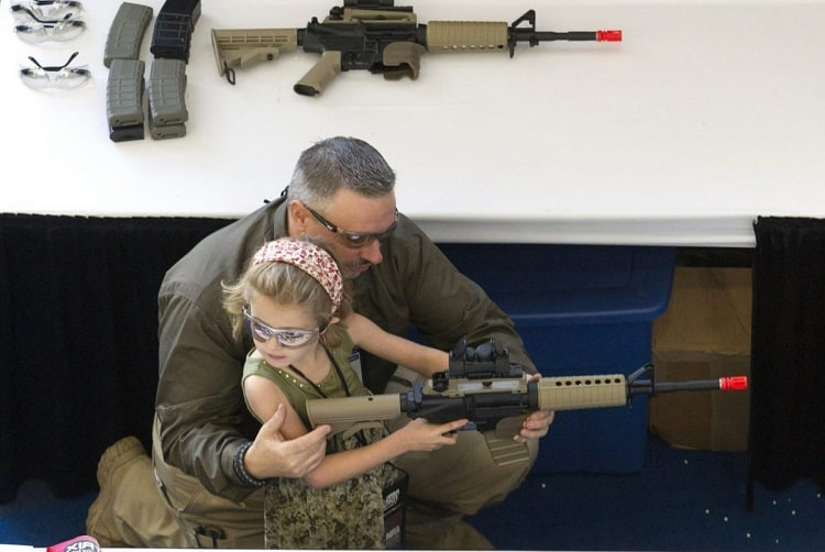 Father Showing Airsoft Rifle To Daughter